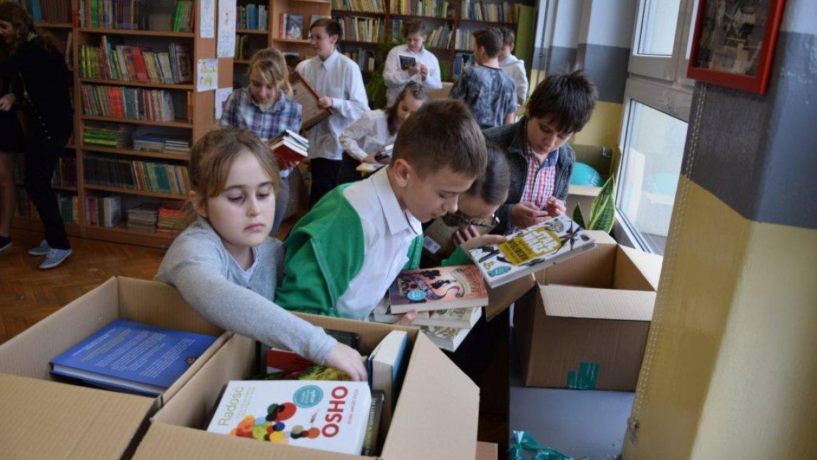 uczniowie wśród pudeł z książkami