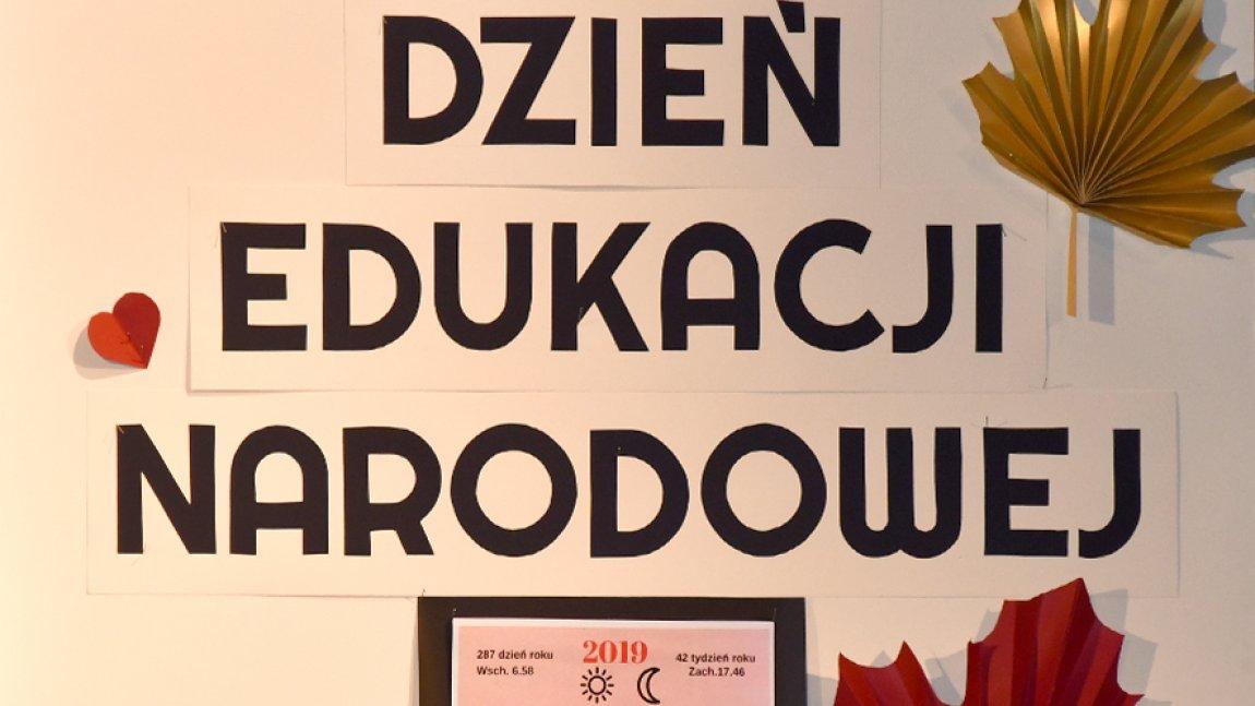 Ilustracja przedstawiająca napis Dzień Edukacji Narodowej przyozdobiony papierowymi liśćmi jesiennymi