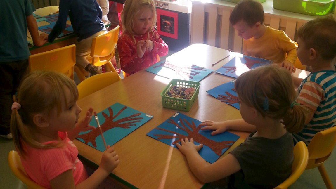 Dzieci siedzące przy stoliku i wykonujące pracę plastyczną
