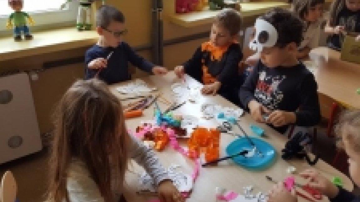 Dzieci siedzące przy stole i wykonujące pracę plastyczną