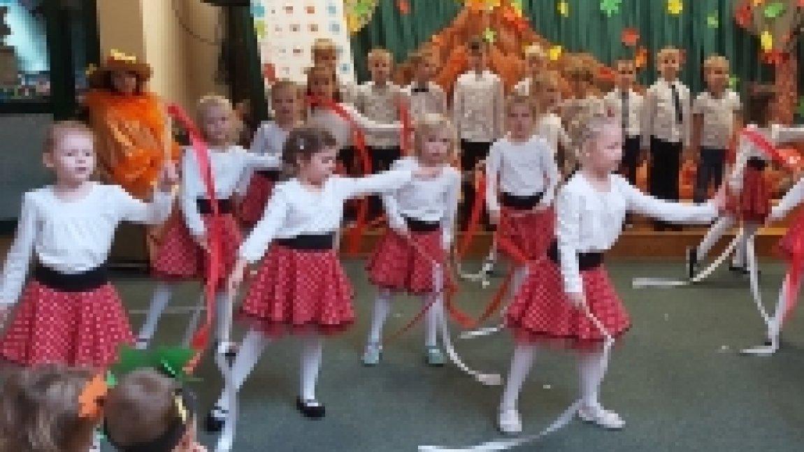 Tańczące dziewczynki w czerwonych spódniczkach w tle chłopcy stojacy na scenie