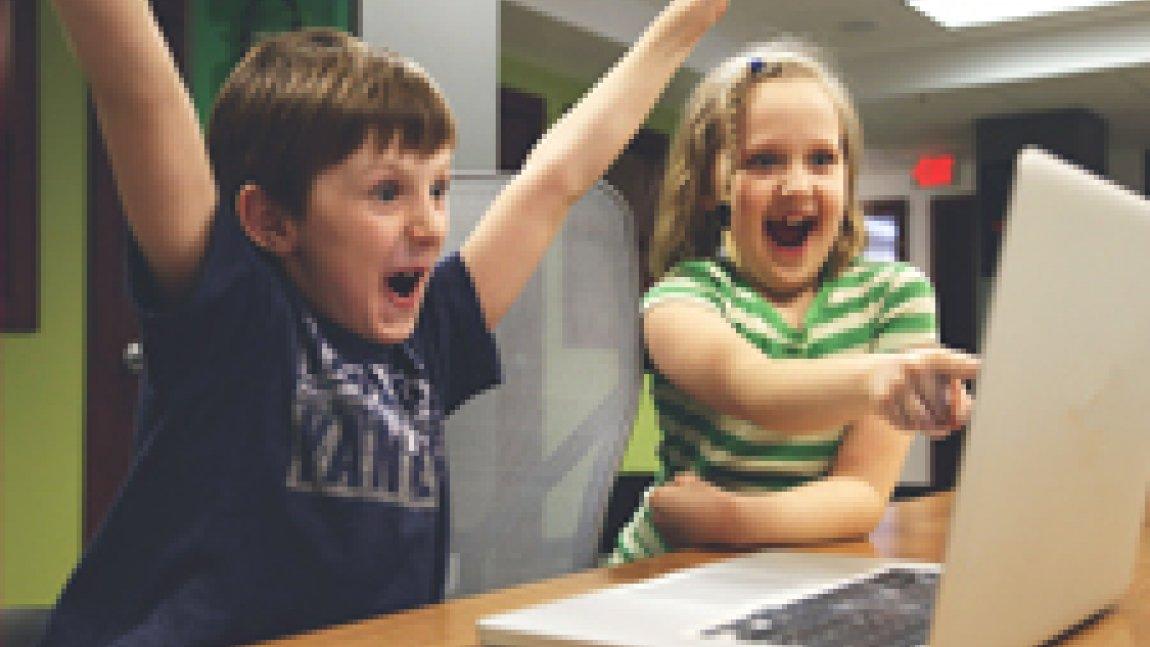 Chłopiec i dziewczynka siedzący przed laptopem