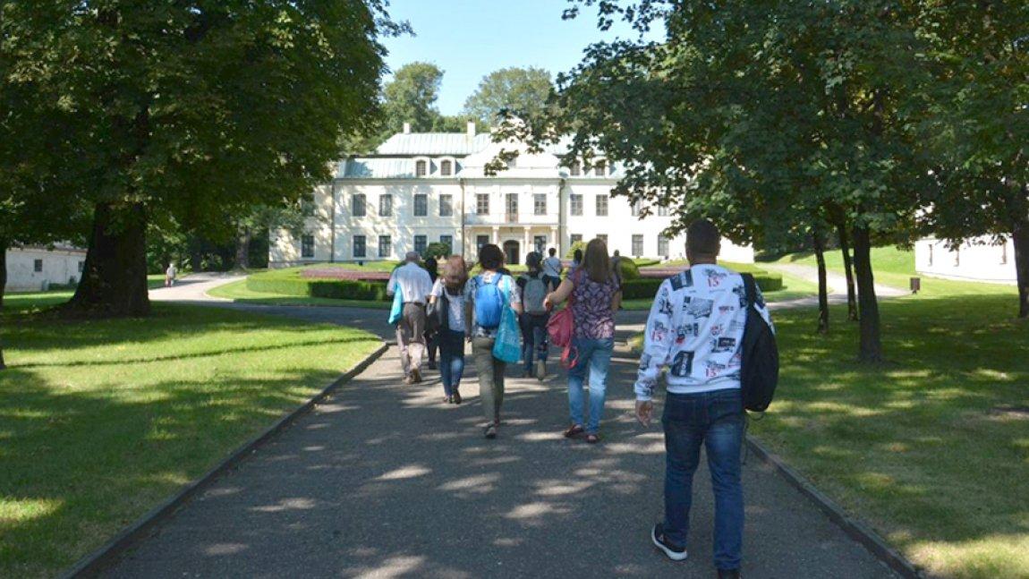 Park przed Pałacem Mieroszewskich, na pierwszym planie grupa ludzi idąca alejką w stronę pałacu.