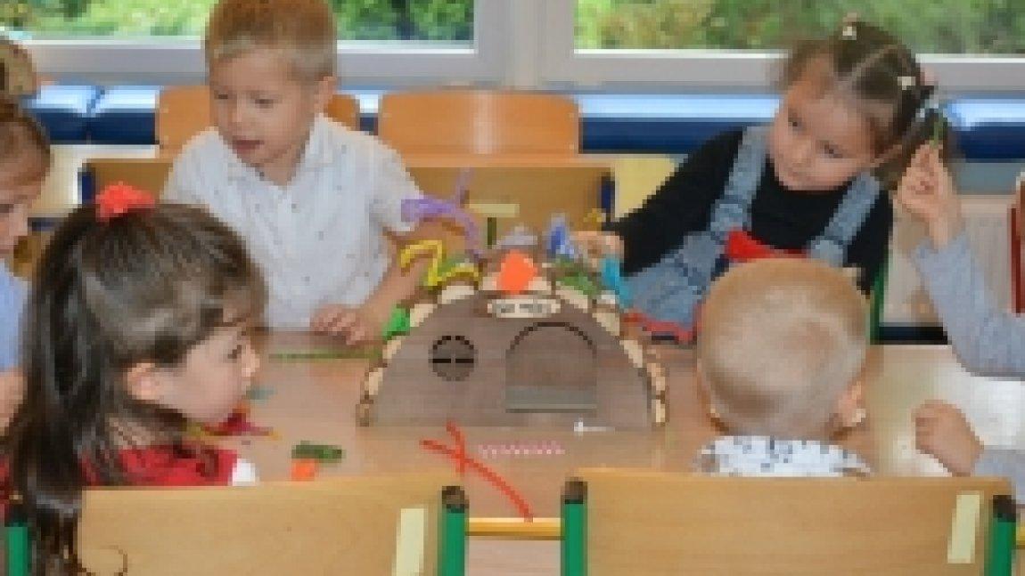 Dzieci siedzące przy stoliku i ozdabiające budkę dla jeży