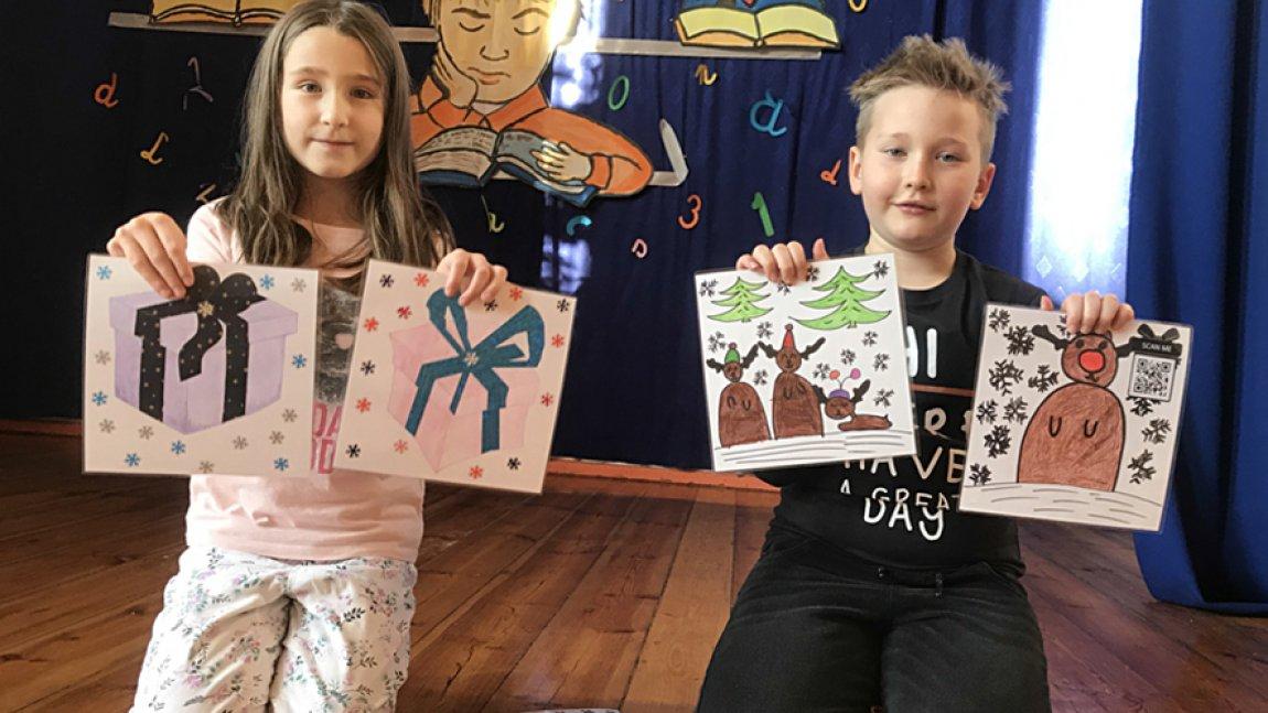 Dziewczynka i chłopiec trzymający prace plastyczne