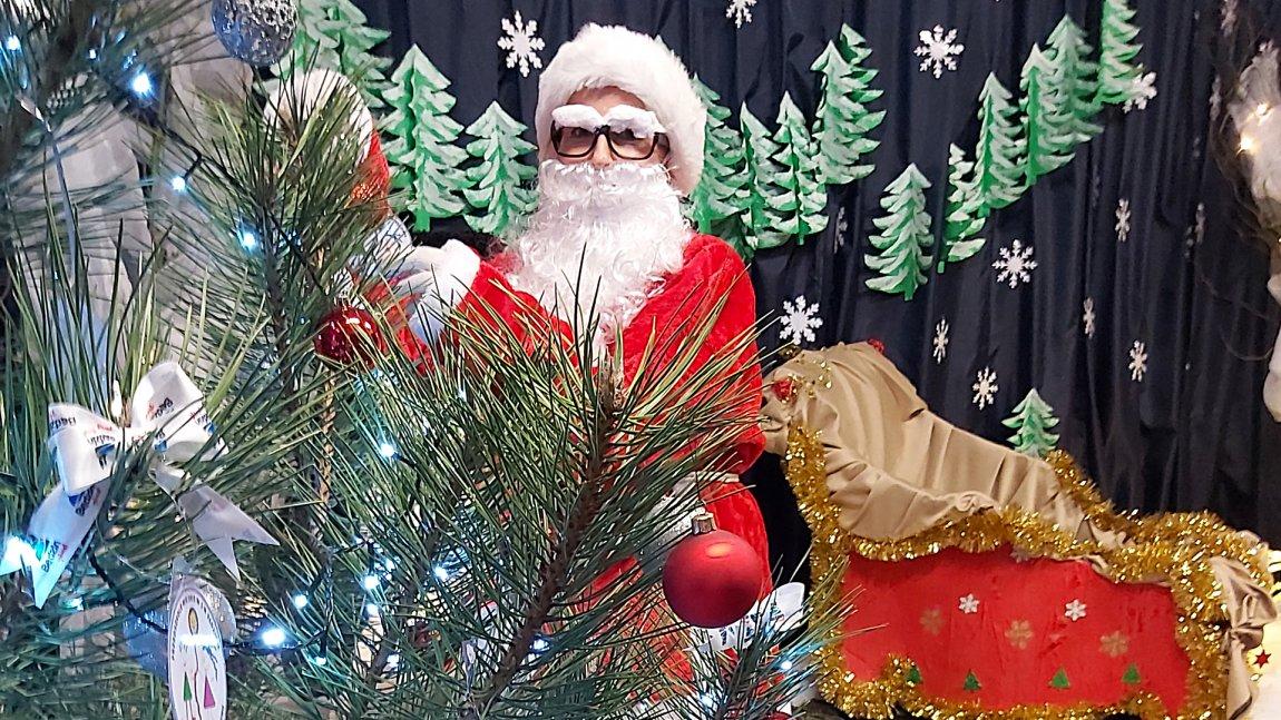 Ilustracja przedstawiająca fragment choinki, Św. Mikołaja na tle dekoracji świątecznych