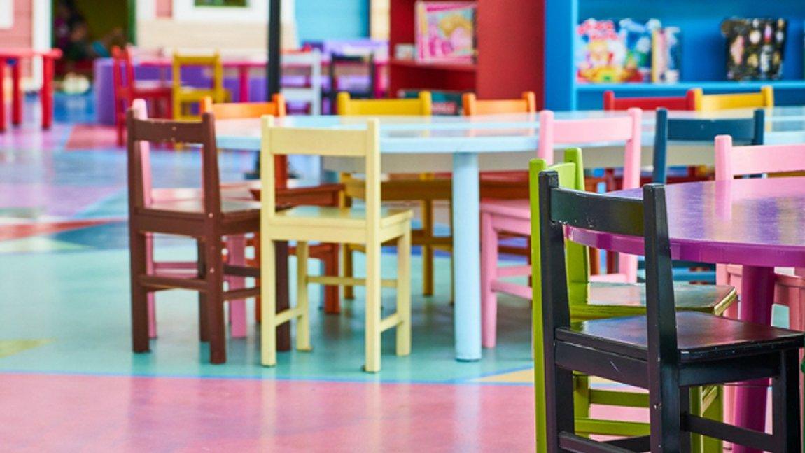 Ilustracja przedstawiająca kolorowe stoliki i krzesła we wnętrzu sali przedszkolnej