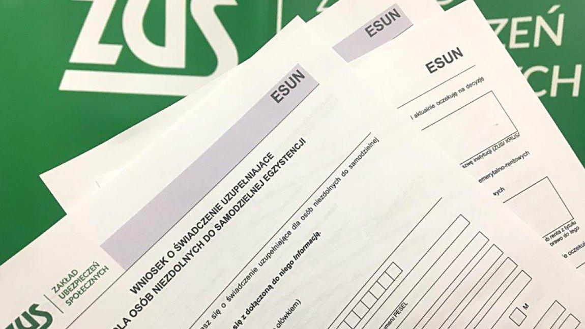 Ilustracja przedstawiająca leżące dokumenty na zielonym tle z logo Zus