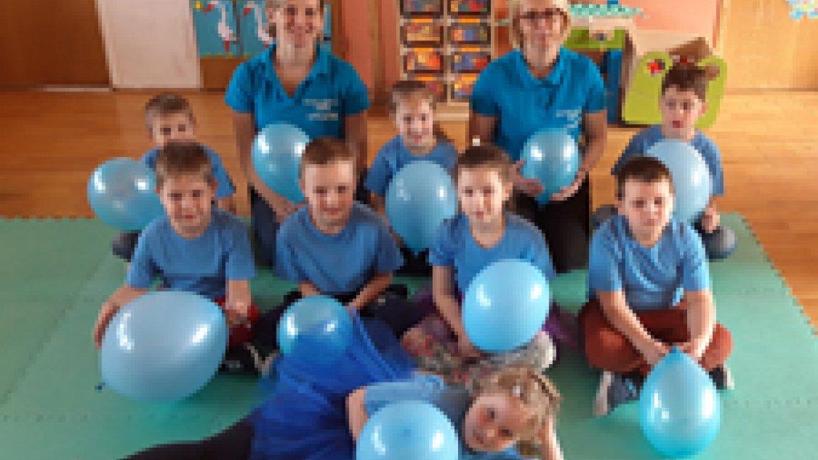 Dzieci ubrane na niebiesko trzymające niebieskie baloniki