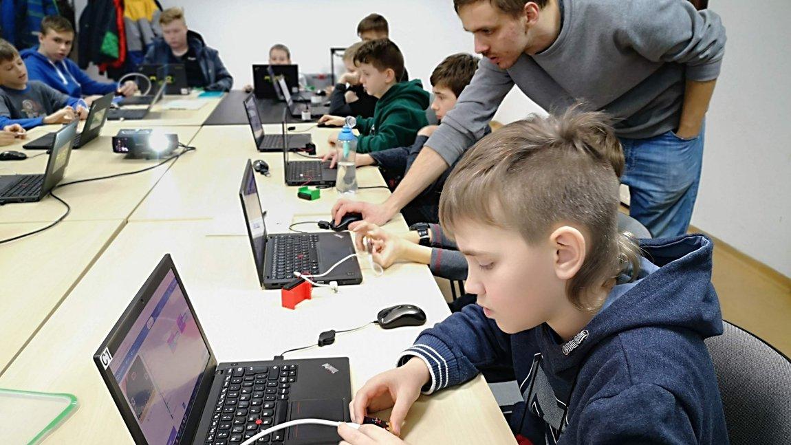 Dzieci siedzące przy laptopach nad nimi pochylający się instruktor