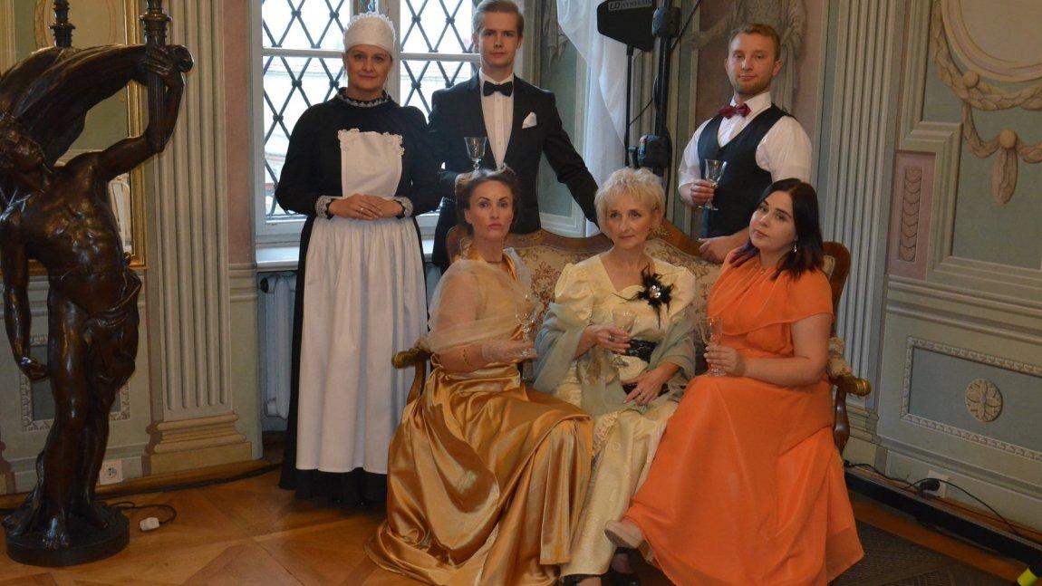 Osoby w strojach dworskich prezentujące się we wnętrzu Pałacu Mieroszewskich